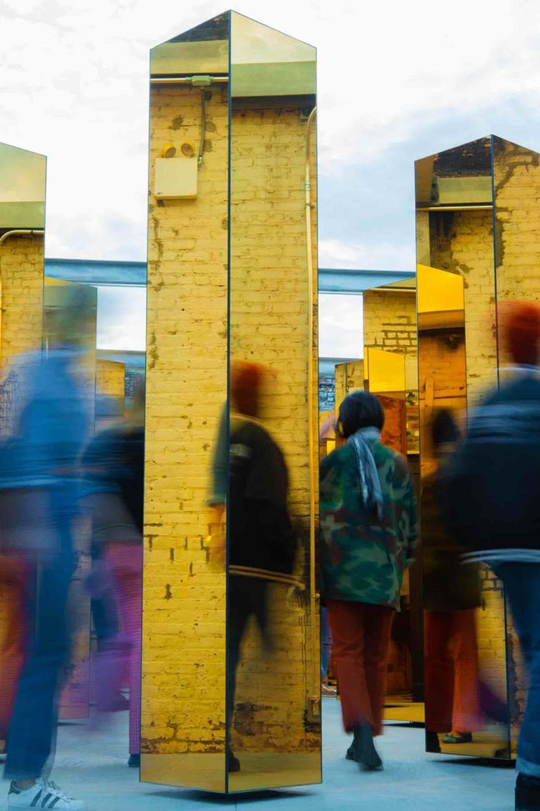 Blurred image of people walking through the installation of yellow mirrored columns.