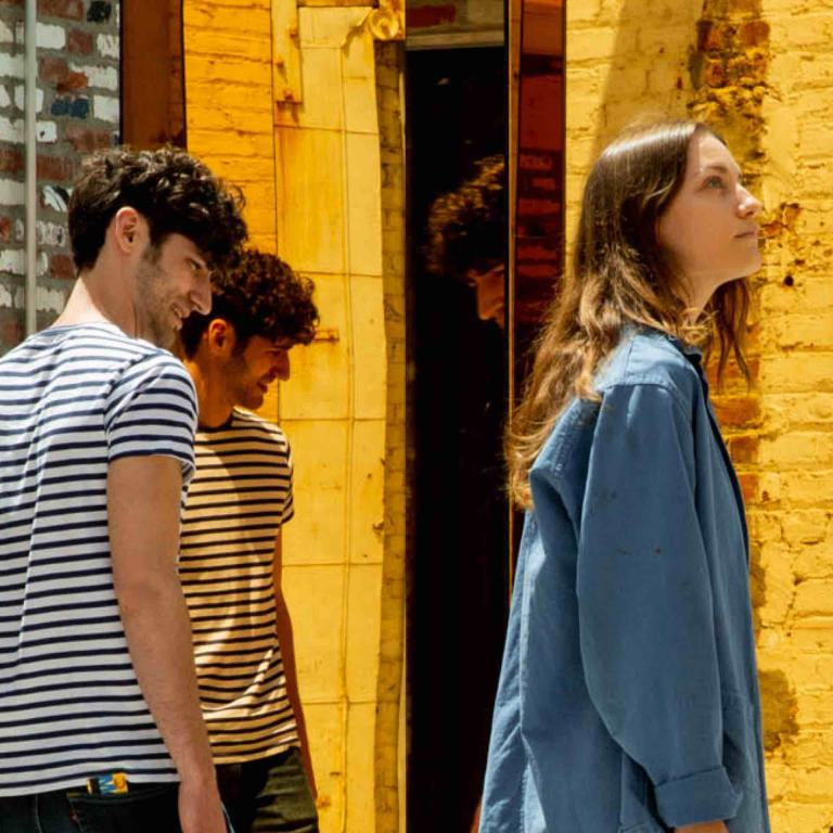 Two young men and a young woman look at yellow mirrored columns and the surroundings that they are reflecting.