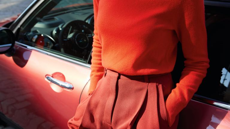 Woman leans against the MINI Clubman