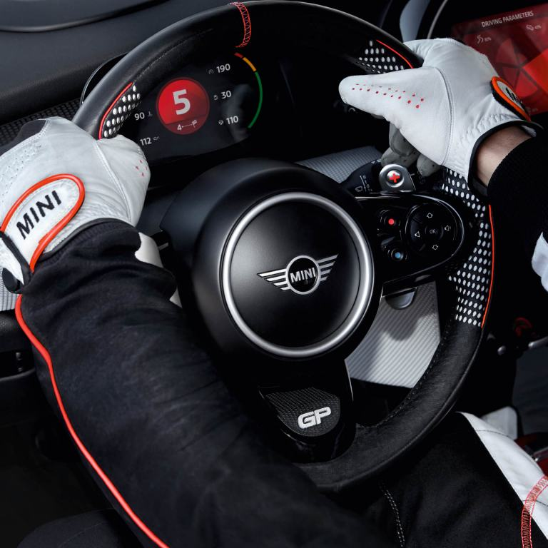 A man in racecar driving gear has his hands on the wheel of a MINI John Cooper Works Concept.