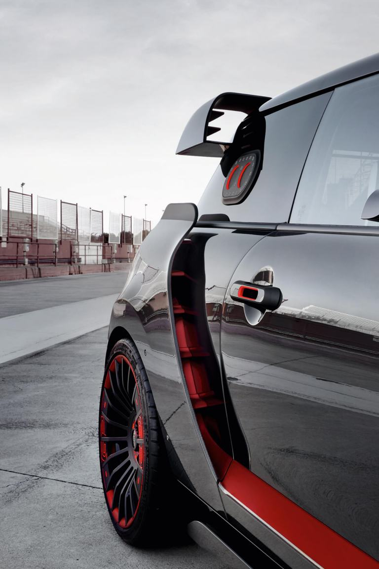A red and black MINI John Cooper Works Concept drives past on a race track.