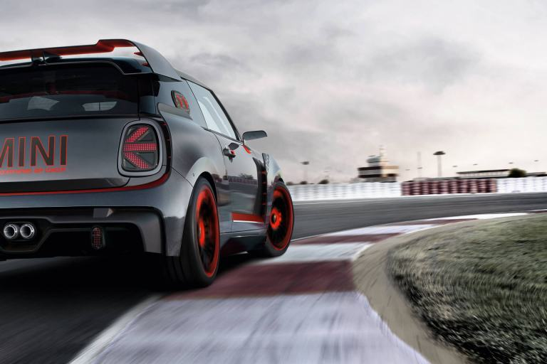 A red and black MINI John Cooper Works Concept is seen from behind on a race track.