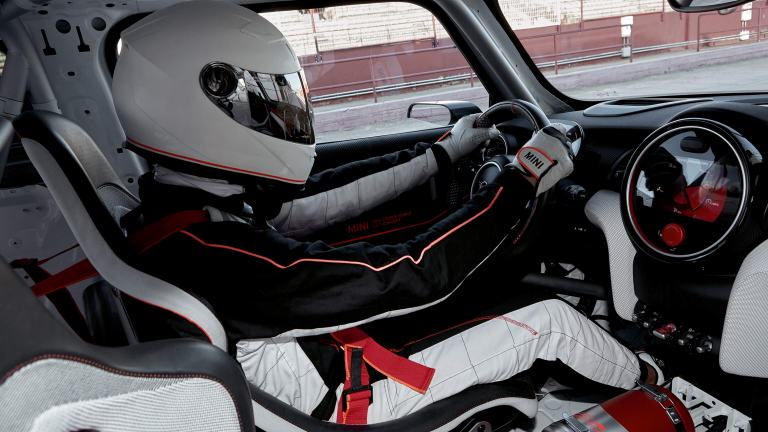 Interior shot: a man in racecar driving gear drives a MINI John Cooper Works Concept.