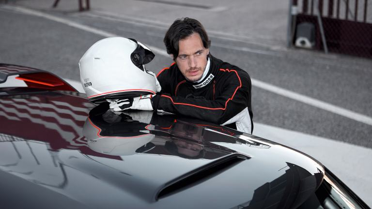 Cool, young man in racecar driving gear leans on the roof of his MINI John Cooper Works Concept.