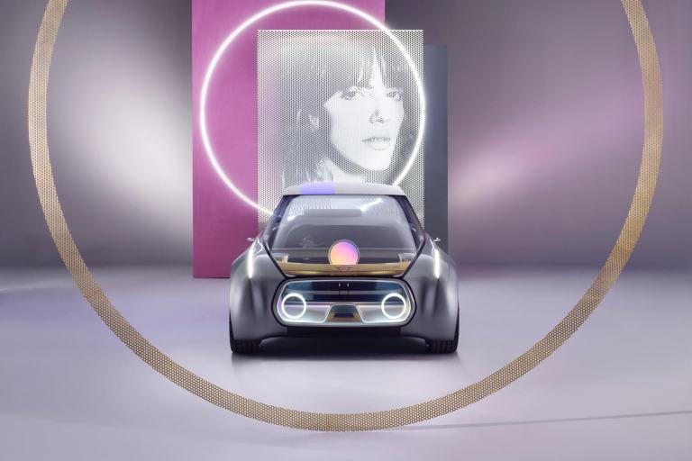 Photograph of a woman is pictured above a MINI VISION NEXT 100, front view.