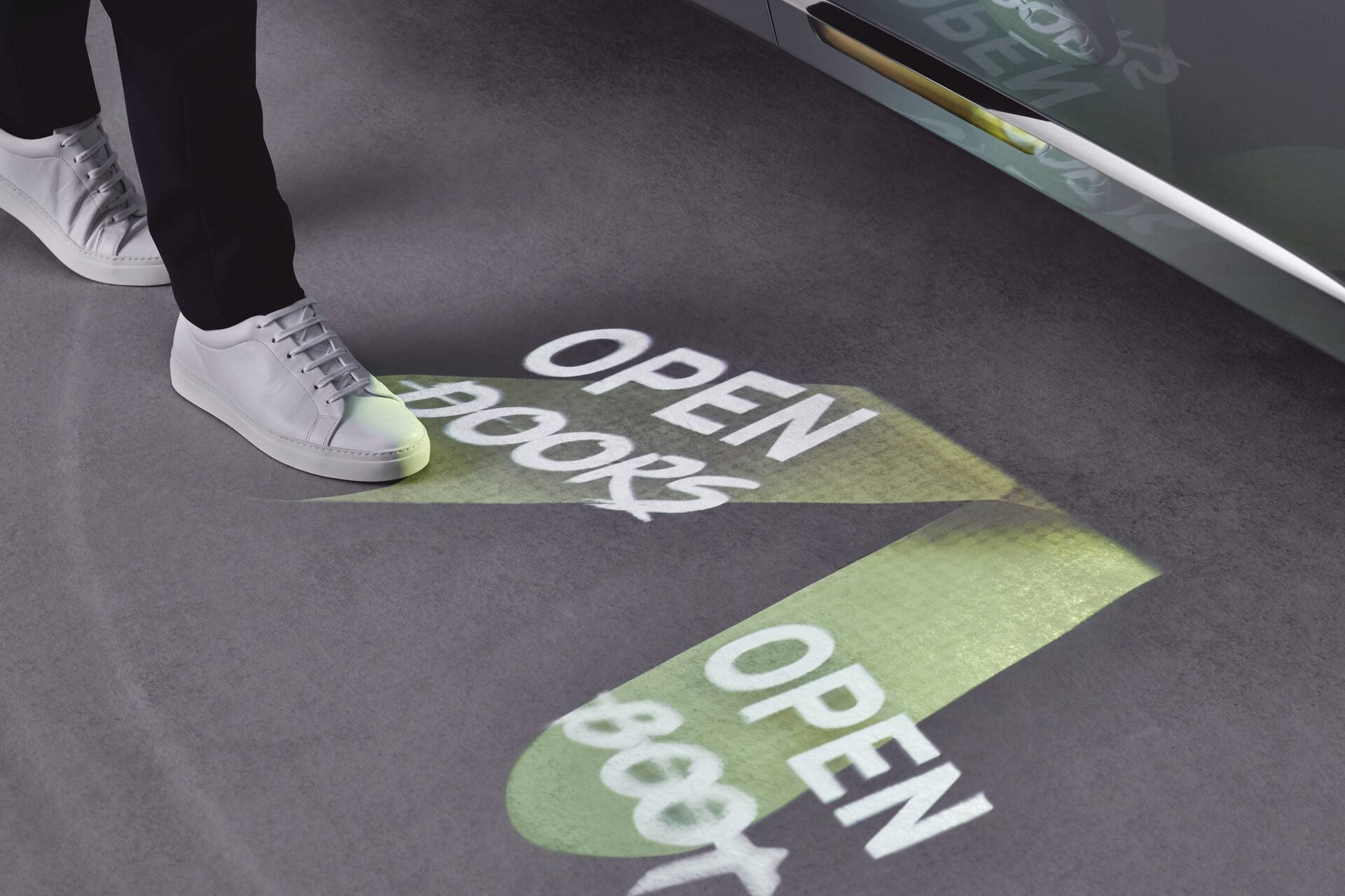Projected foot controls on the ground beside a MINI VISION NEXT 100 – OPEN DOORS, OPEN BOOT.