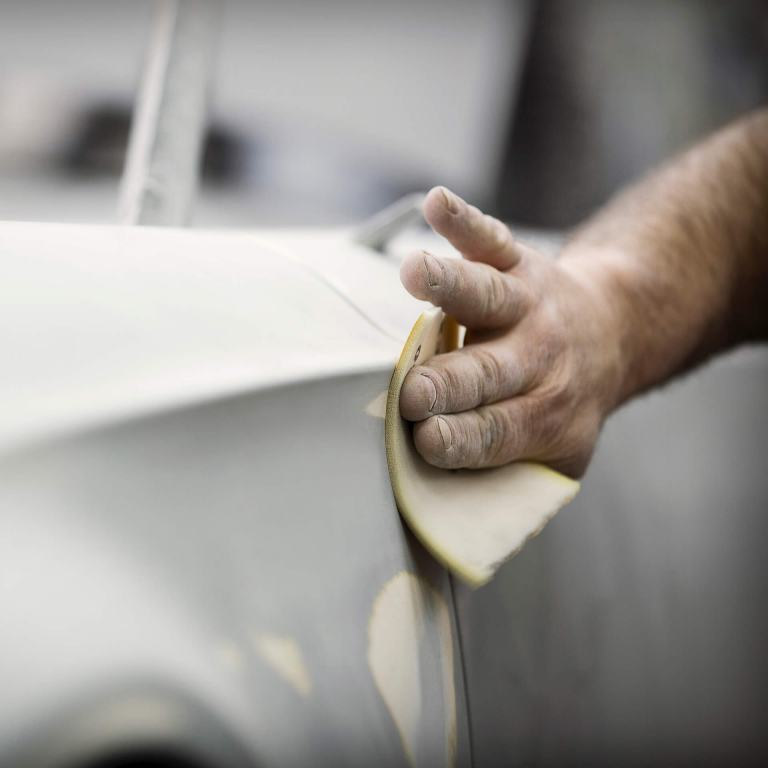 Factory worker puts the finishing touches on a new MINI Superleggera with sandpaper.