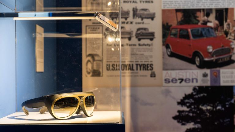 Gold racing glasses with a built-in camera are displayed in a glass case.