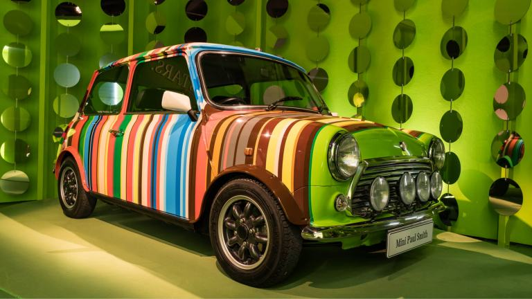 A vintage MINI painted with vertical rainbow stripes