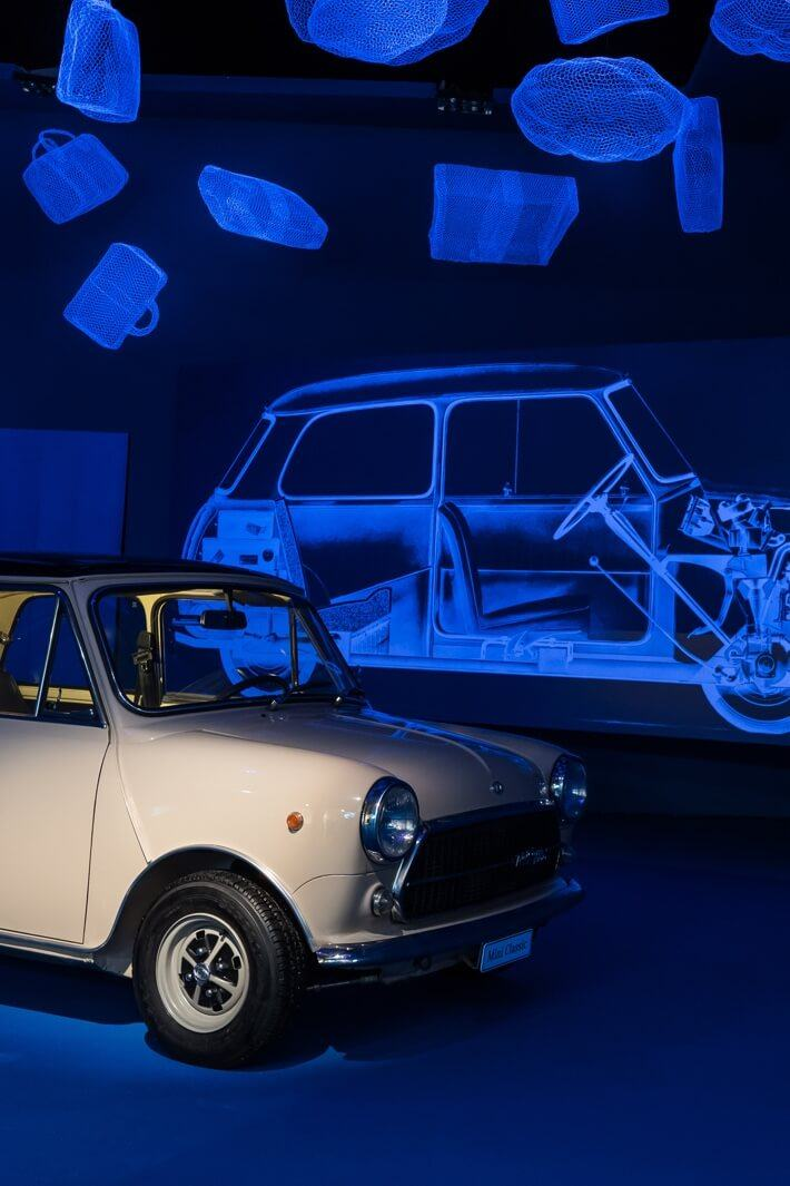 A white vintage MINI parked in front of a black light poster of its inner workings.