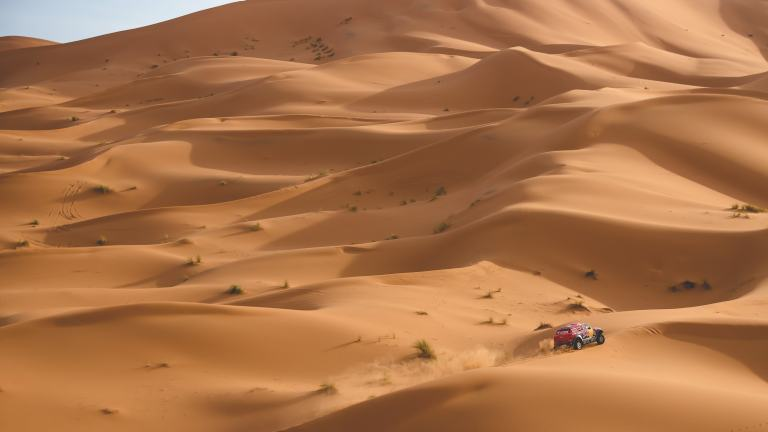 A tiny MINI ALL4 Racing car almost disappears in what seems like endless sand dunes.