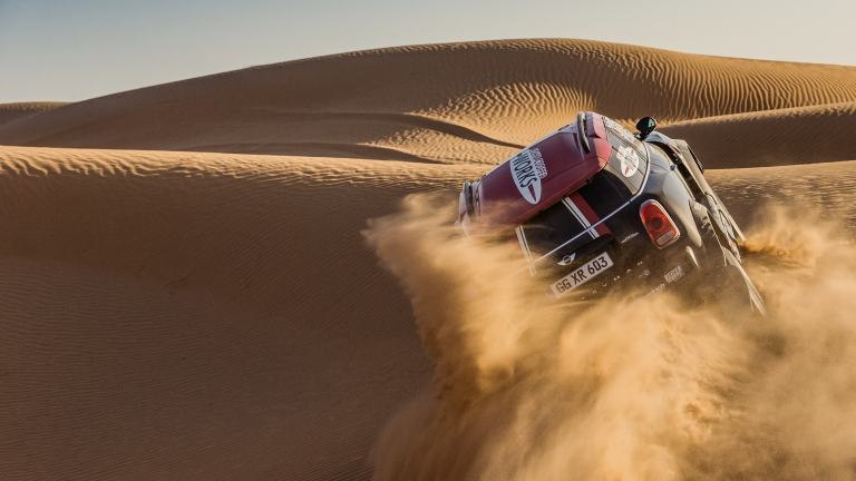 MINI John Cooper Works Rally car leaves a cloud of sand in its wake while tearing up a dune.