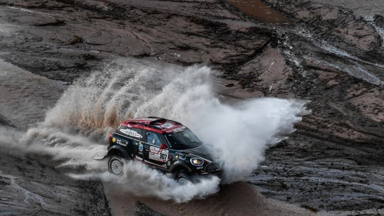 Overhead view of the MINI John Cooper Works Rally driving through a mountain stream, sending a jet of spray into the air at the Dakar Rally 2018.