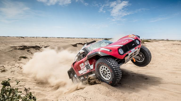 MINI John Cooper Works Buggy driving up a sand dune on its rear wheels at Dakar Rally 2018.