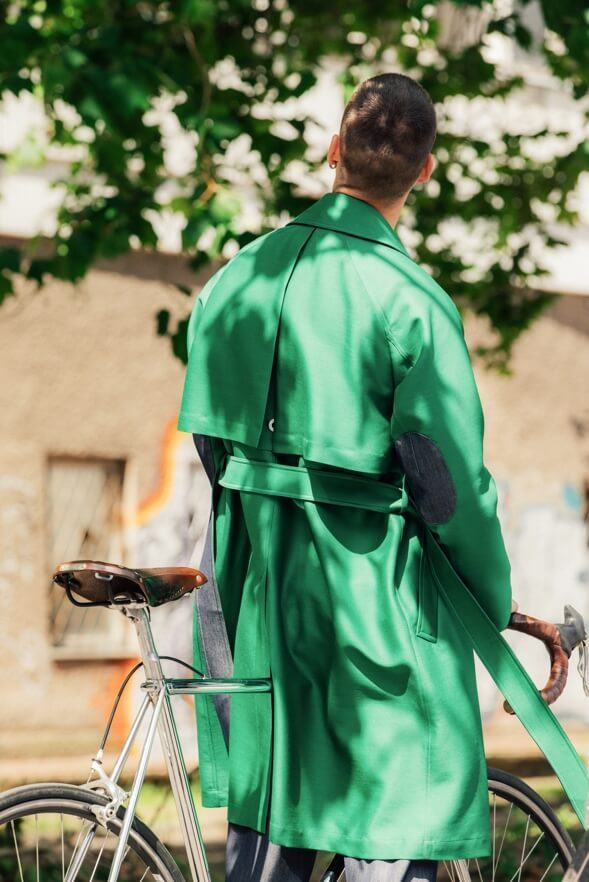 Man, on a silver bike wears a green coat by Staffonly.