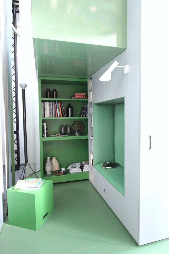 Minimal study in green with books, reading nook and light
