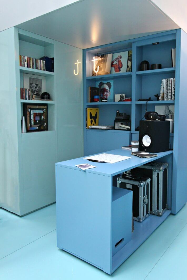 Blue shelving and storage units with vinyl records, a speaker, headphones, CDs and storage boxes