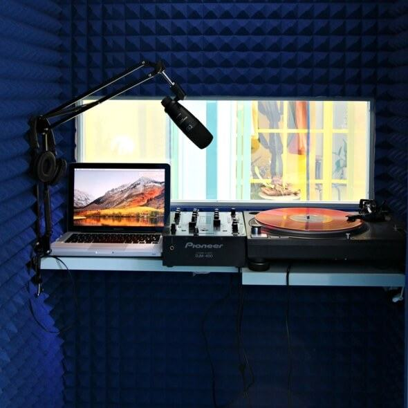 Blue soundproofing foam lines a tiny recording studio with a microphone and vinyl turntable.