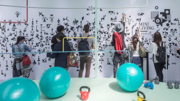 Young men and women explore the MINI LIVING exhibit at Salone del Mobile 2018. Colourful exercise equipment is in the foreground.