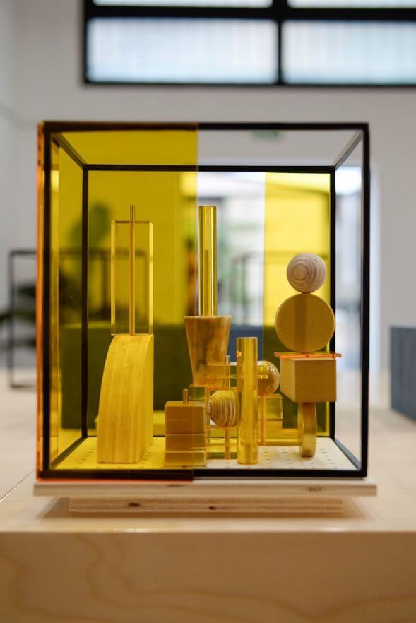 Close-up of a finished living space model featuring wooden blocks and  yellow screens in a black frame.