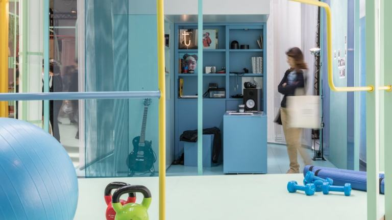 Woman stands in a tiny blue study containing a blue desk and stool as well as a black guitar. Exercise equipment is visible in the foreground.