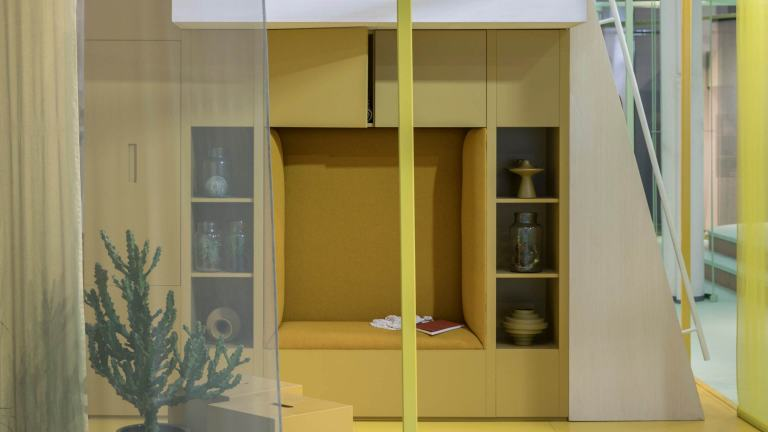 Small living room in yellow with a reading nook build into the wall cabinets