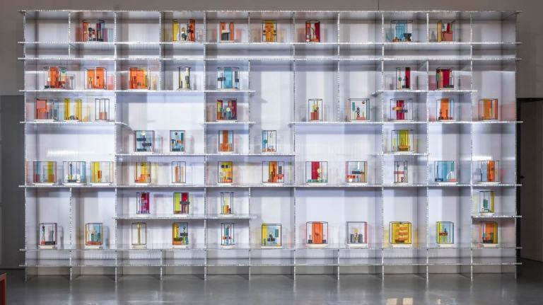 A large white shelf unit full of colourful, abstract totem models